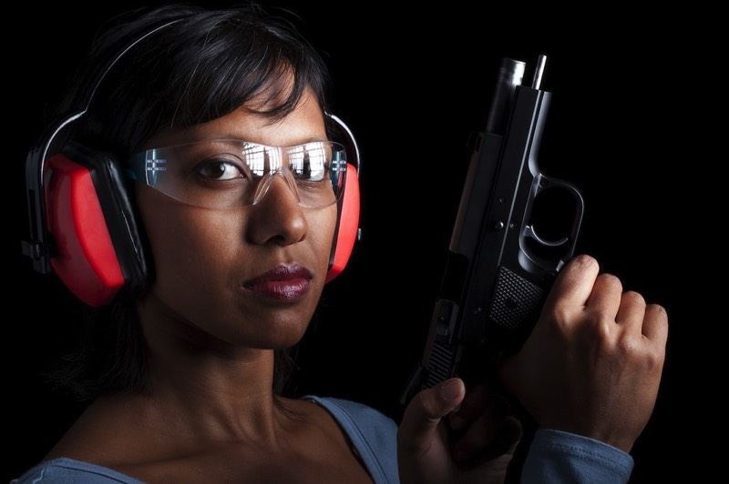 Woman practicing self-defense at gun range